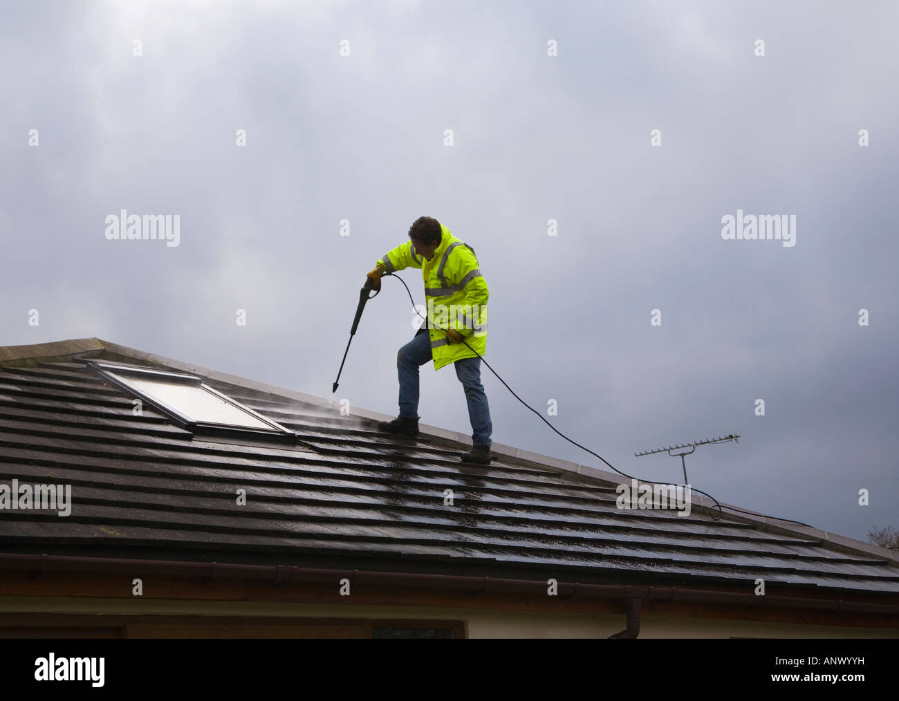 Man cleaning the roof of a house using a high pressure water jetwash stock photo royalty free - Using water pressure roof cleaning ...