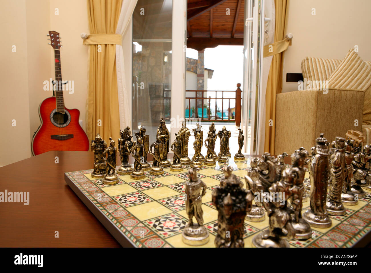 Exotic Chess Set With Guitar And View Through Window To Sun Patio In  Background