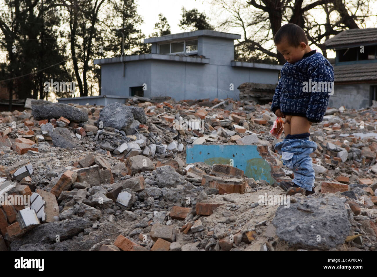 PEE ON ALLSITUATION IN CHINA Stock Photo - a boy peeing in a neighbourhood Hutong partially destroyed  and marked for demolition Beijing China