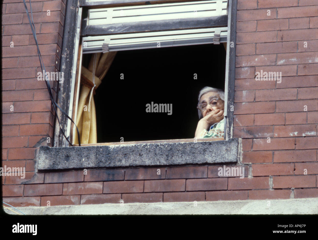Brick Apartment Building Window elderly woman glances out an open window in an old brick apartment