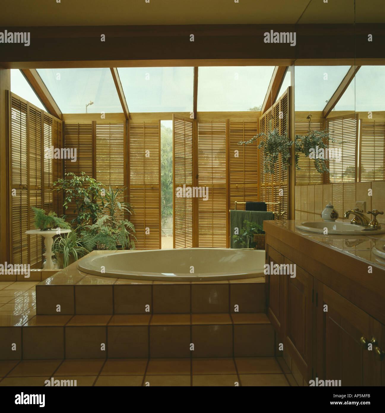 Raised Circular Bath In Modern Bathroom Extension With Plantation Shutters  On Tall Windows