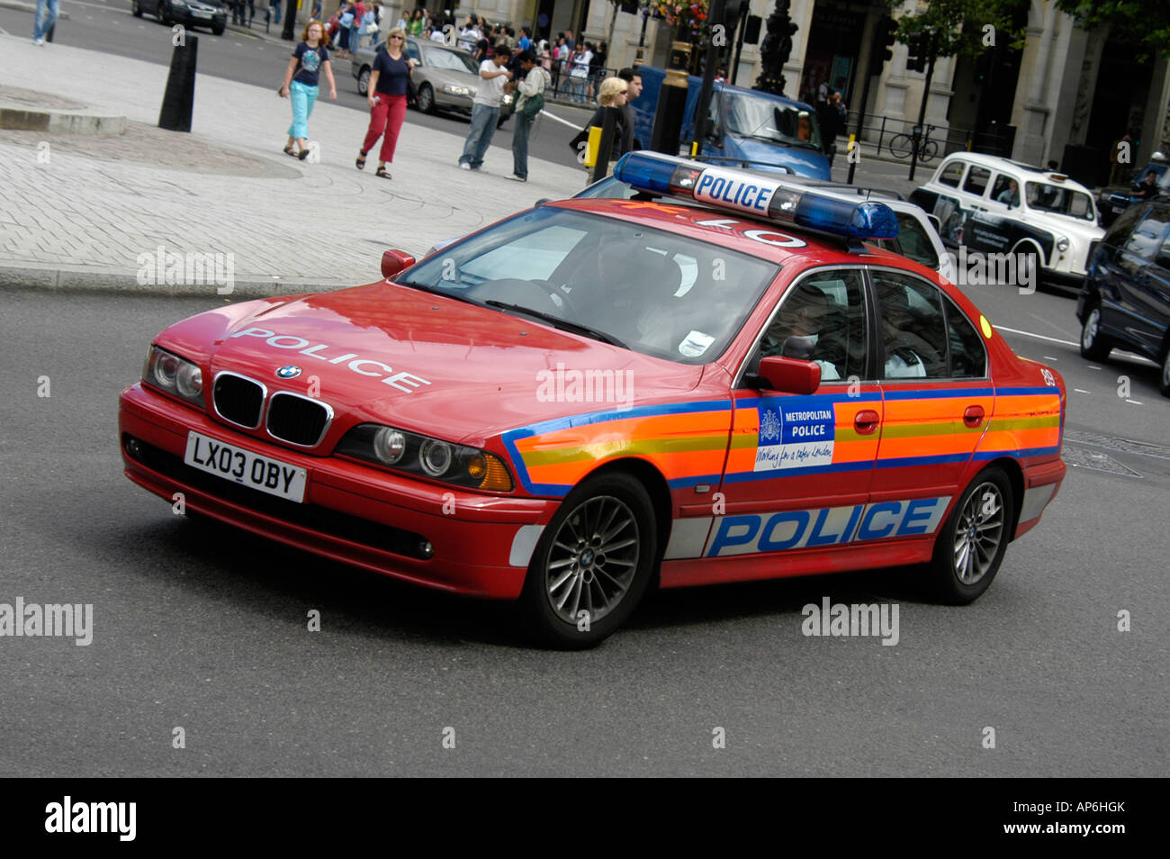 Red bmw police car driving through the city of london england stock image