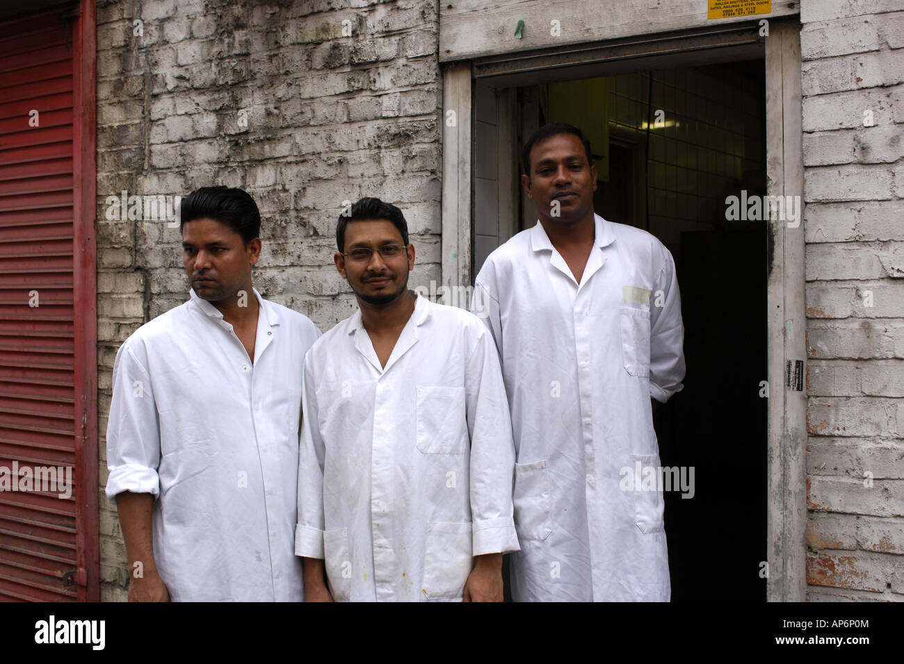 Three Asian Men Wearing White Coats Outside An Halal Butchers ...