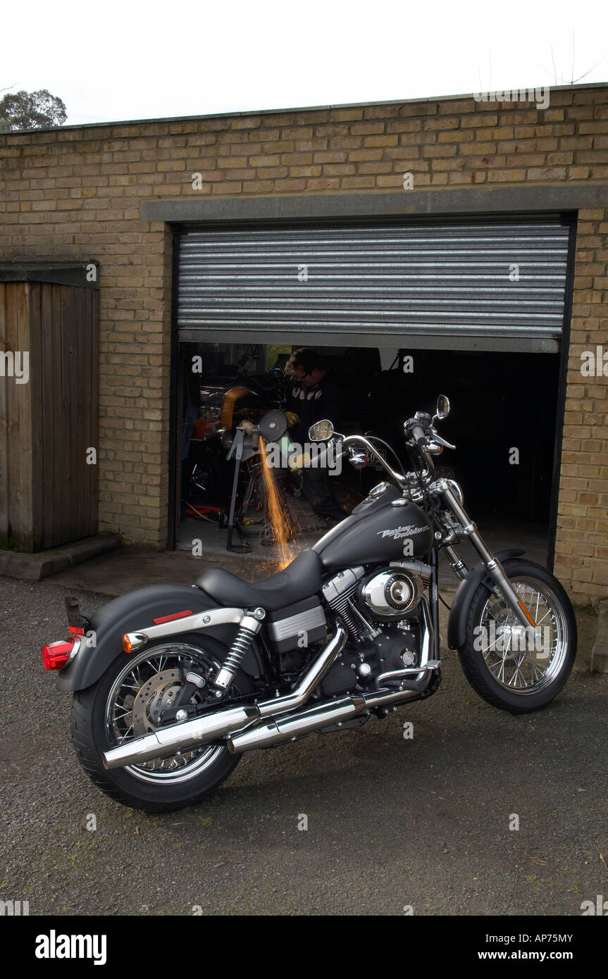 Harley davidson parked outside garage with person angle for Garage a persan