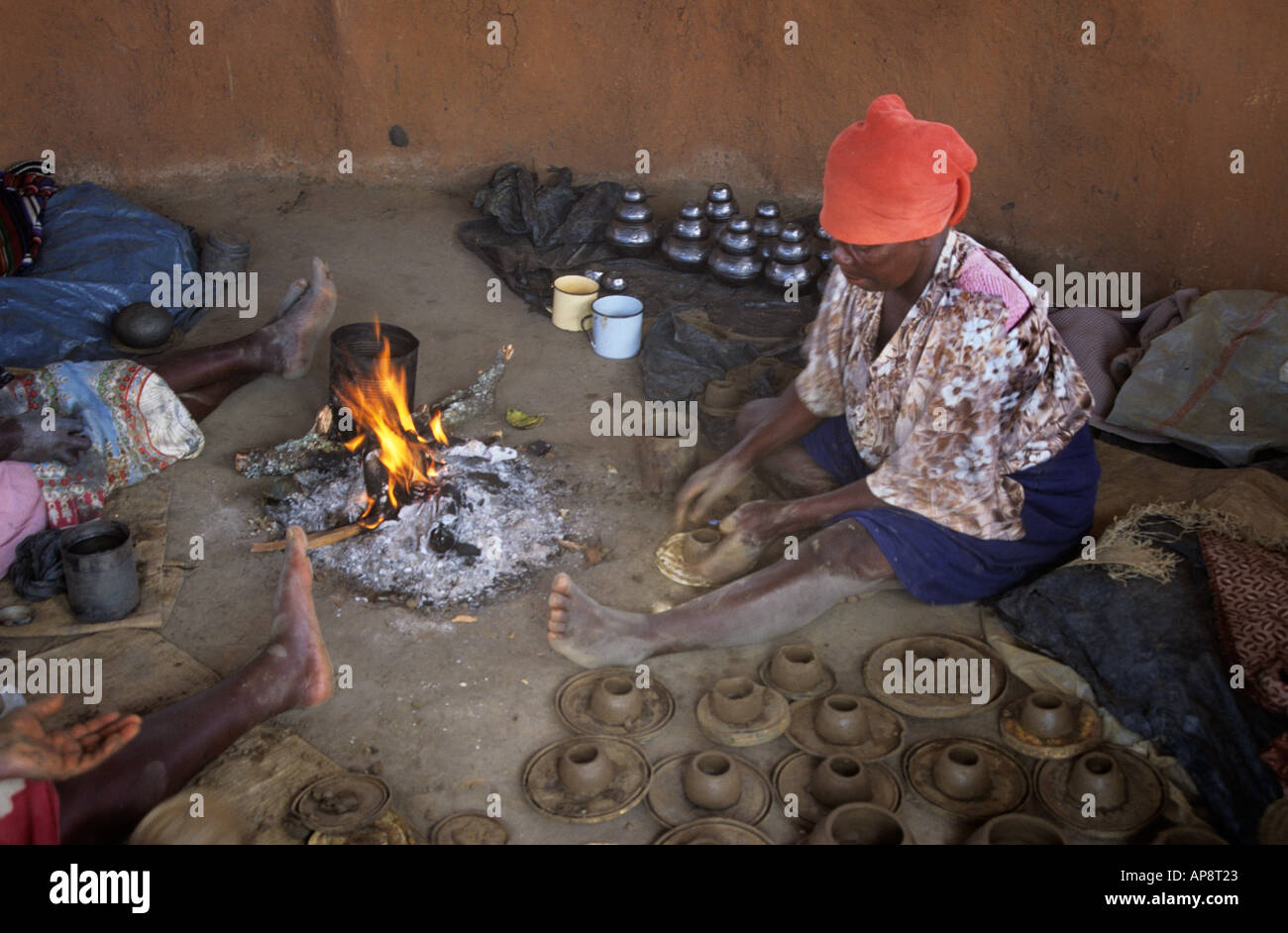 African Woman In A Mud Hut Making Clay Pots Beside An Open
