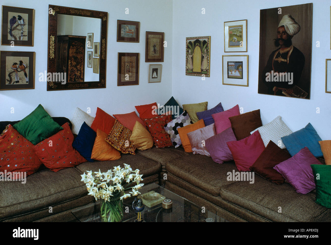 Colourful silk cushions piled on corner seating in sixties living ...