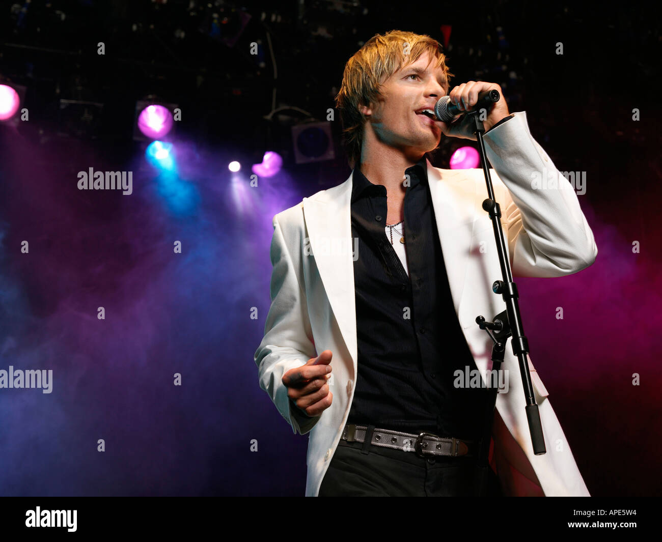 Young Man Singing into microphone on stage at Concert, low ...