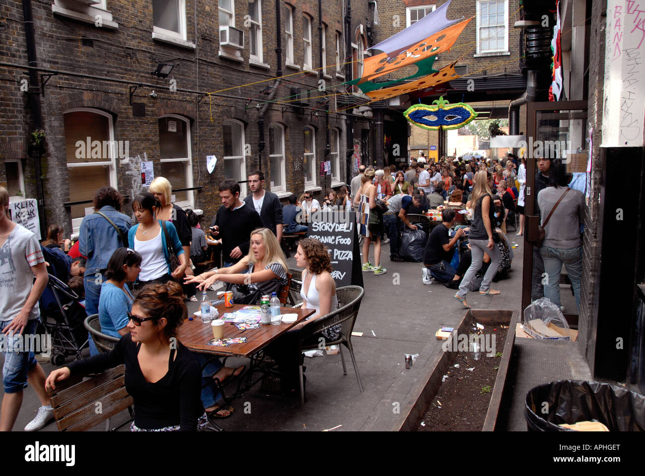 young people eating drinking outside pub off brick lane