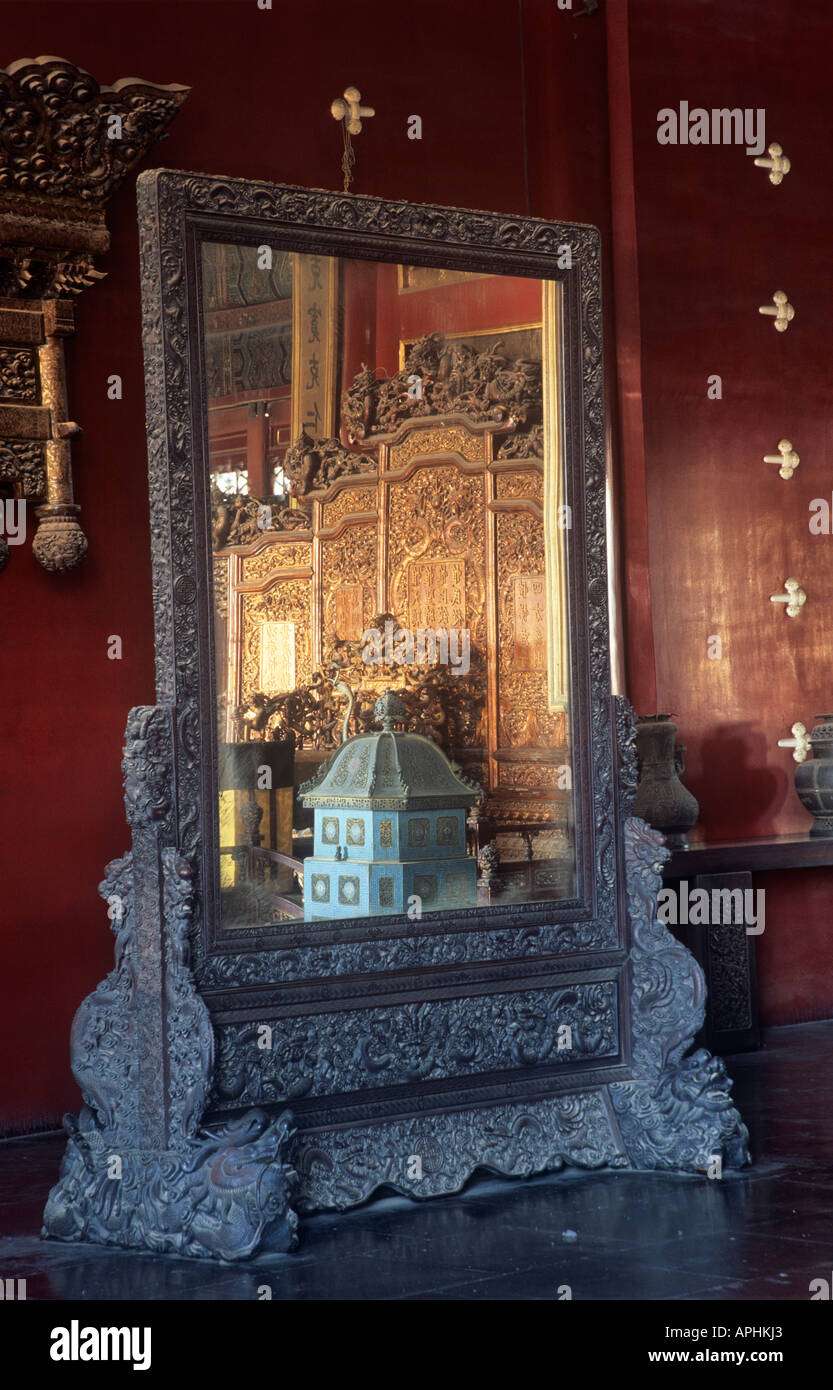 Intricately carved mirror reflecting the carved bedroom furniture