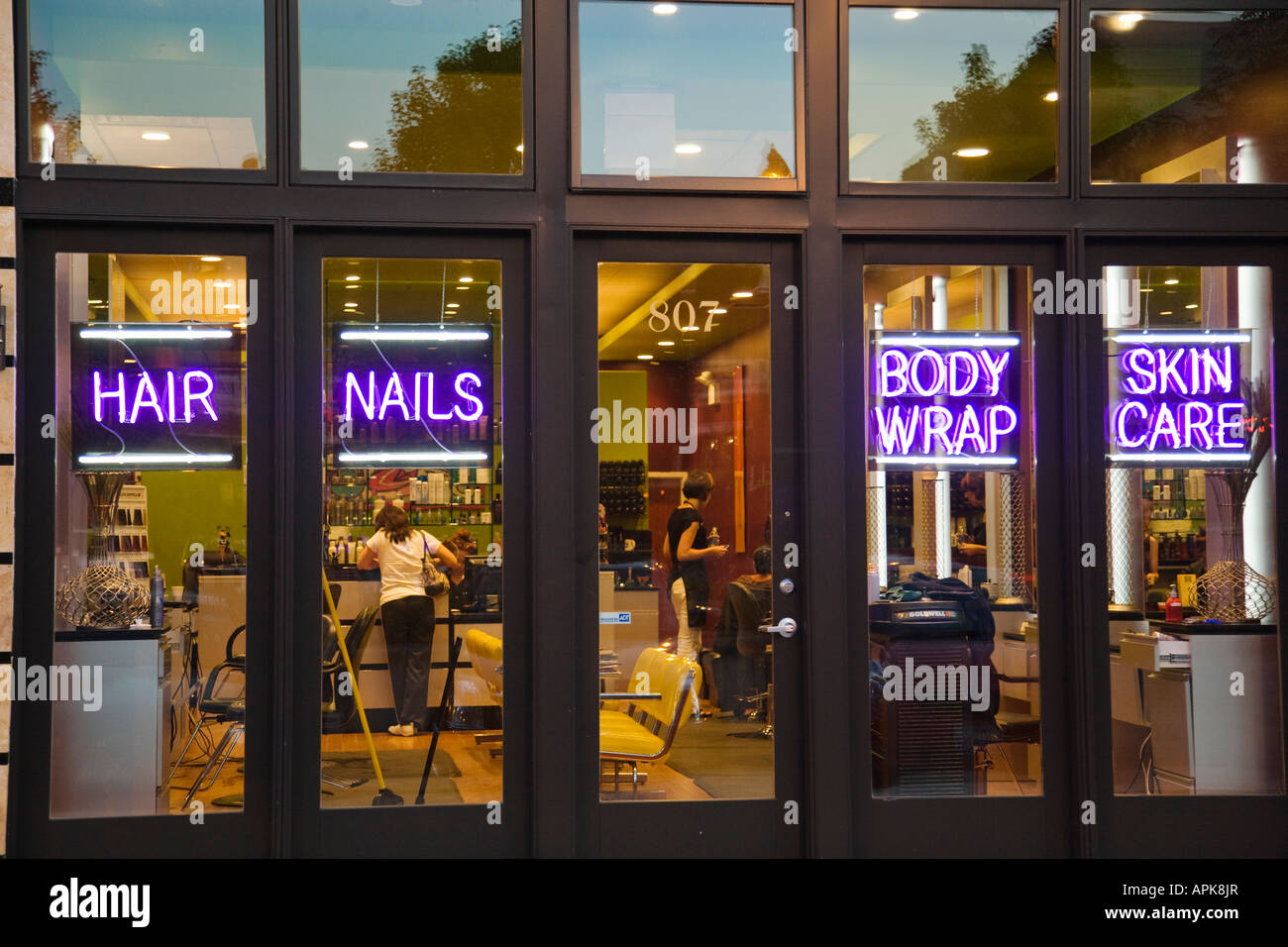 ILLINOIS Chicago Neon Signs For Hair Nails Body Wrap In Window Of Beauty Salon Customers Inside Exterior Building