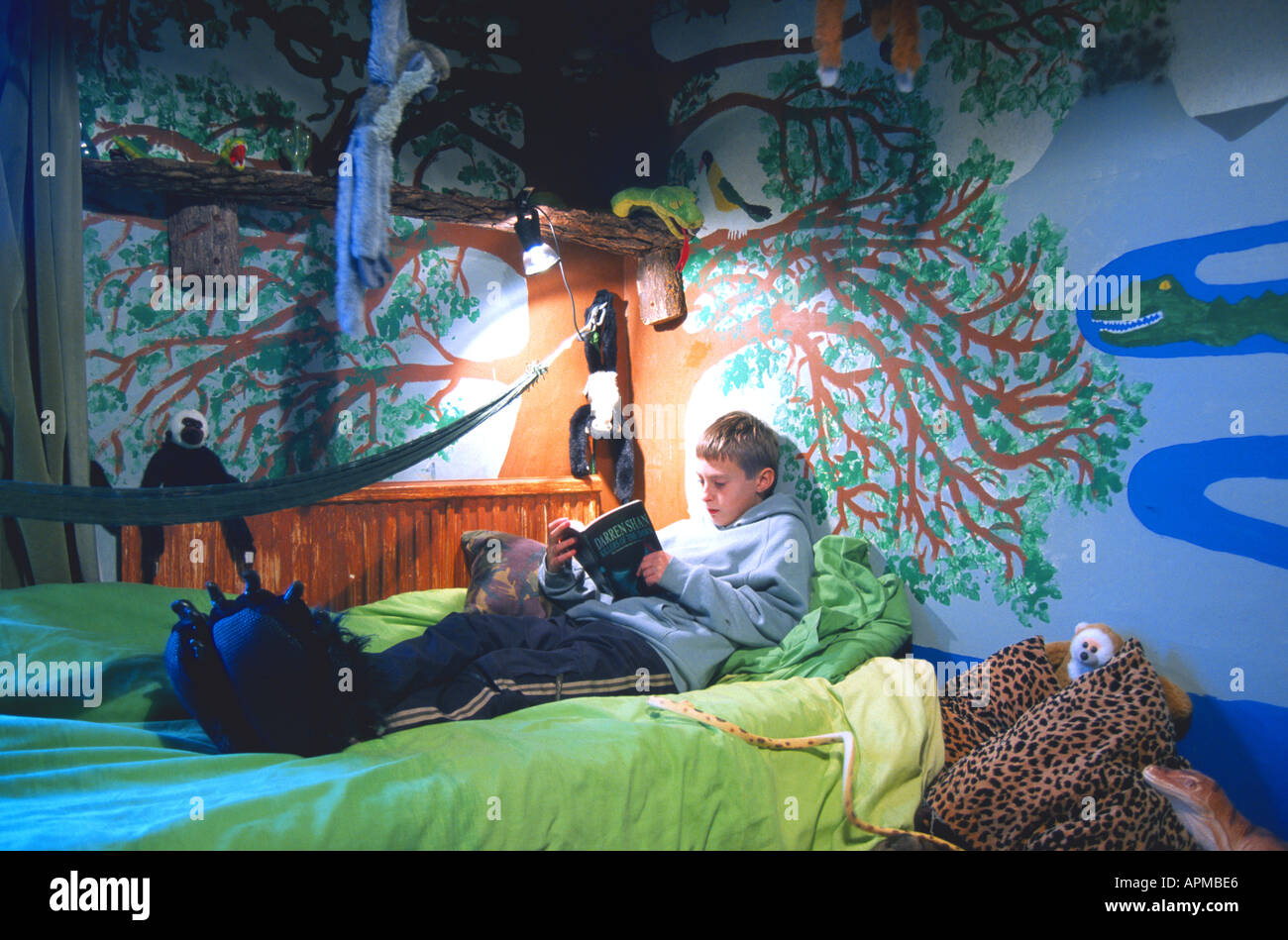 Boy reading in bedroom decorated like jungle fantasy Oscar Hanna. Boy reading in bedroom decorated like jungle fantasy Oscar Hanna