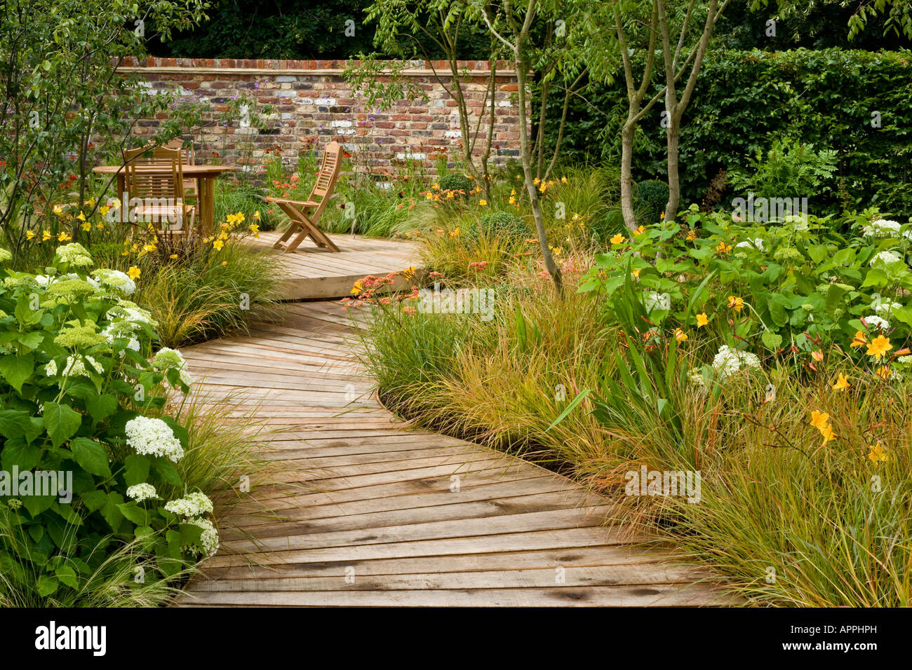 Boardwalk in garden to decking sitting area with table and for Garden decking and grass