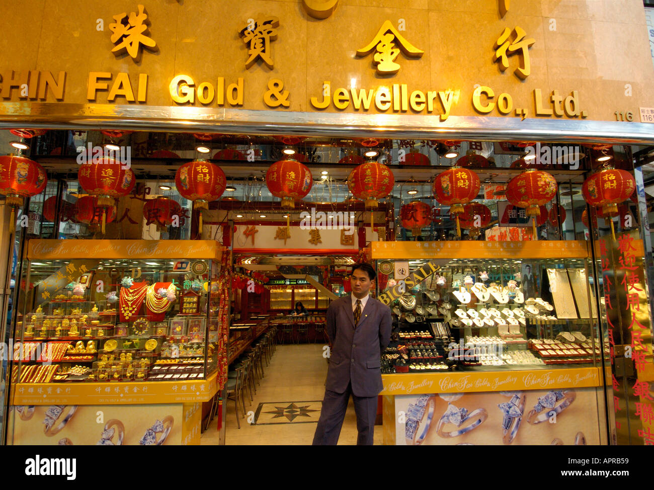 a s assistant stands outside a gold jewellery shop in hong a s assistant stands outside a gold jewellery shop in hong kong 2005
