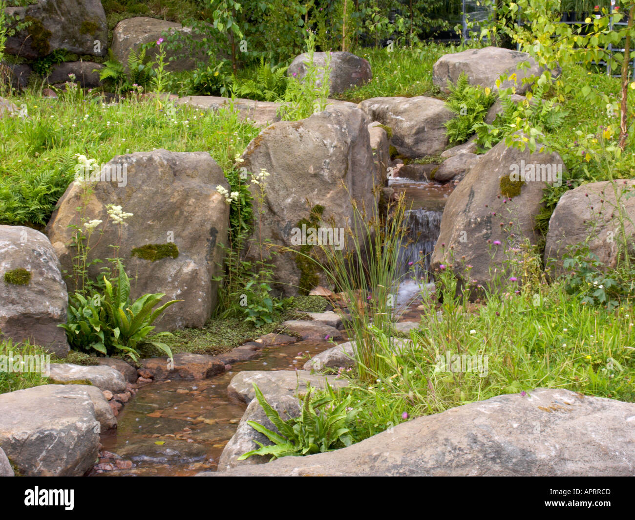 Stock Photo   Tatton Flower Show Waterfall Running Through Boulder Garden  With Natural Planting