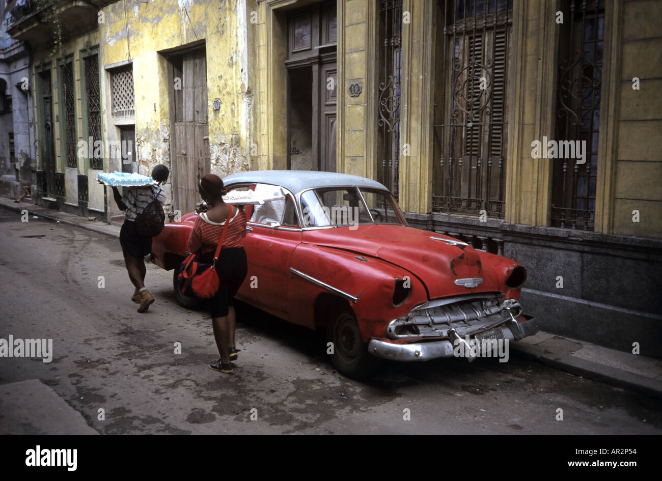 Local women carrying cakes passing by old Fifties car Old Havana