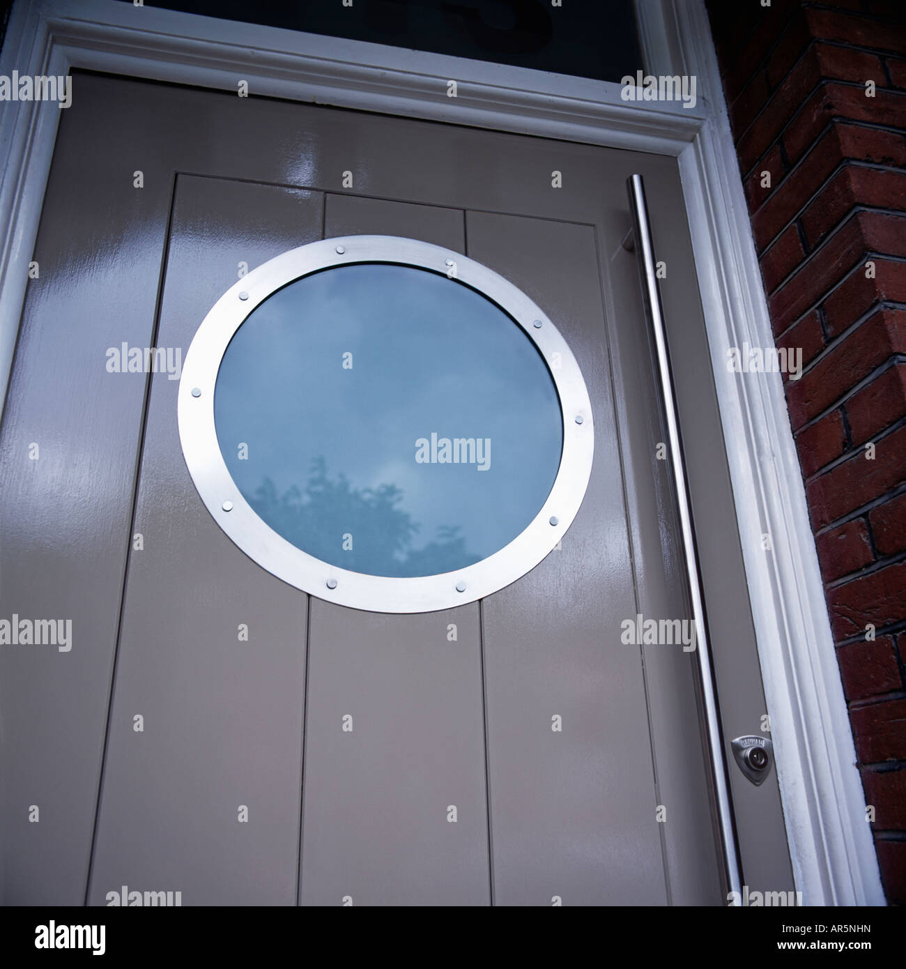 Close up of circular porthole window in modern grey front door ...