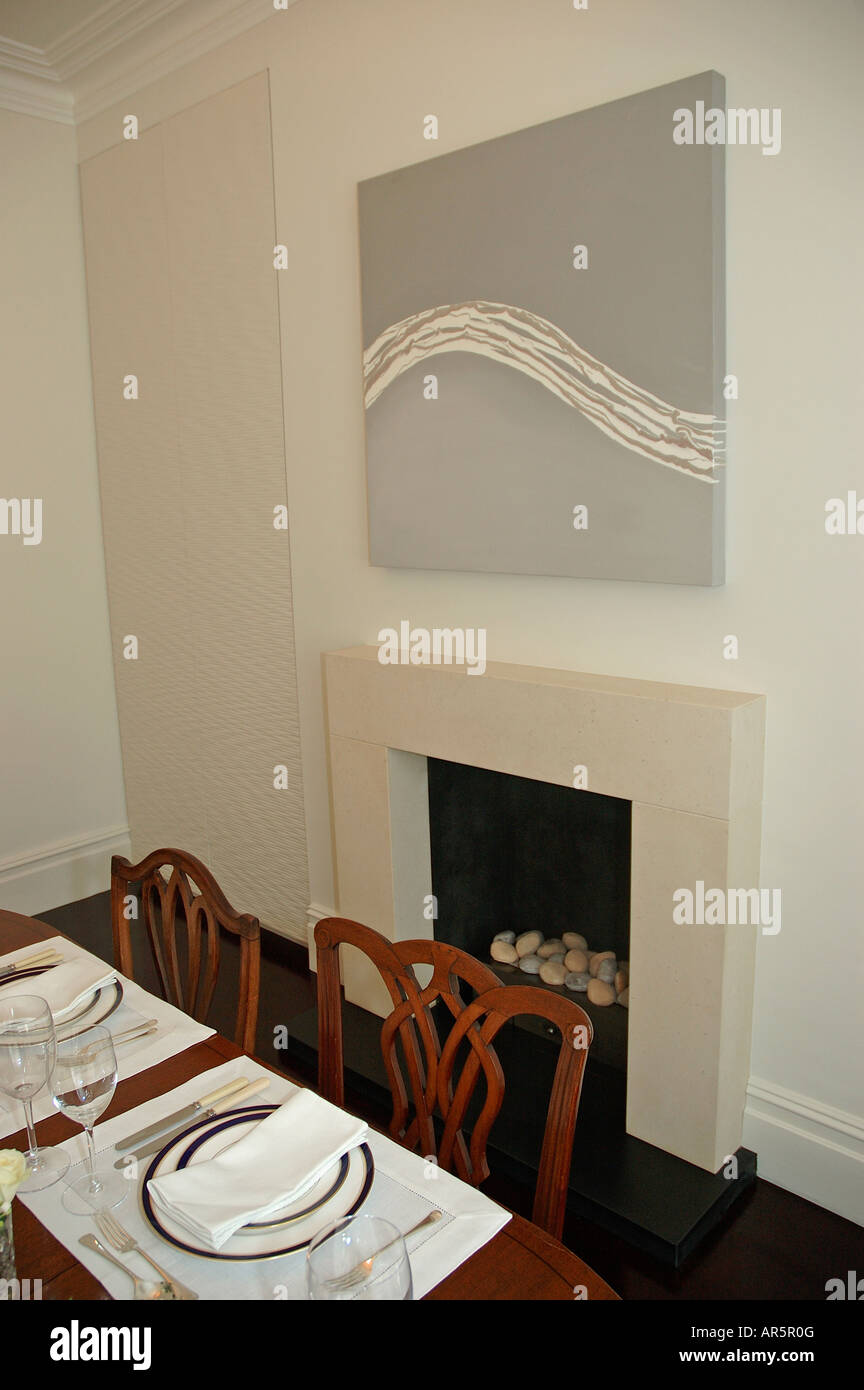 abstract painting above fireplace in modern dining room with white