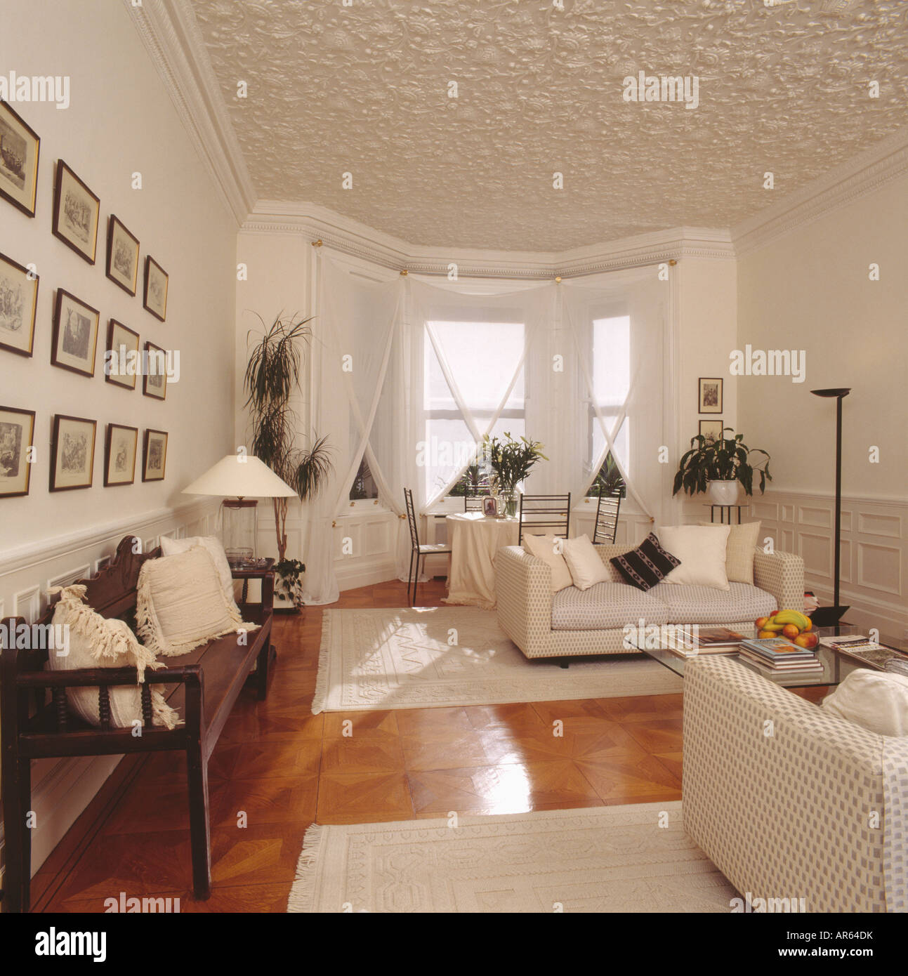 Stock photo textured ceiling in white living room with wooden settle and white sofas cream rugs on polished wooden flooring