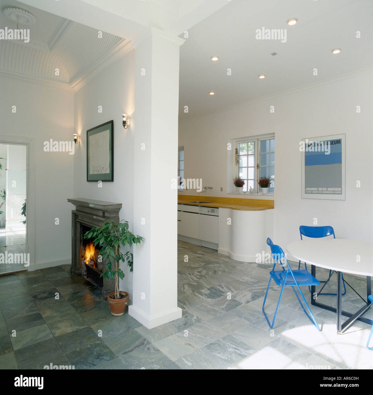 Fireplace On Dividing Wall Of Openplan Kitchen Dining Room With Grey Floor Tiles And Blue Chairs White Table