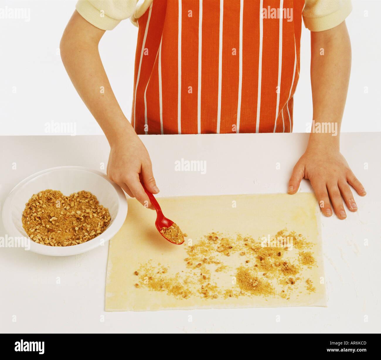 White apron food - Hand Model Wearing And Orange And White Apron Sprinkling Chopped Hazelnuts
