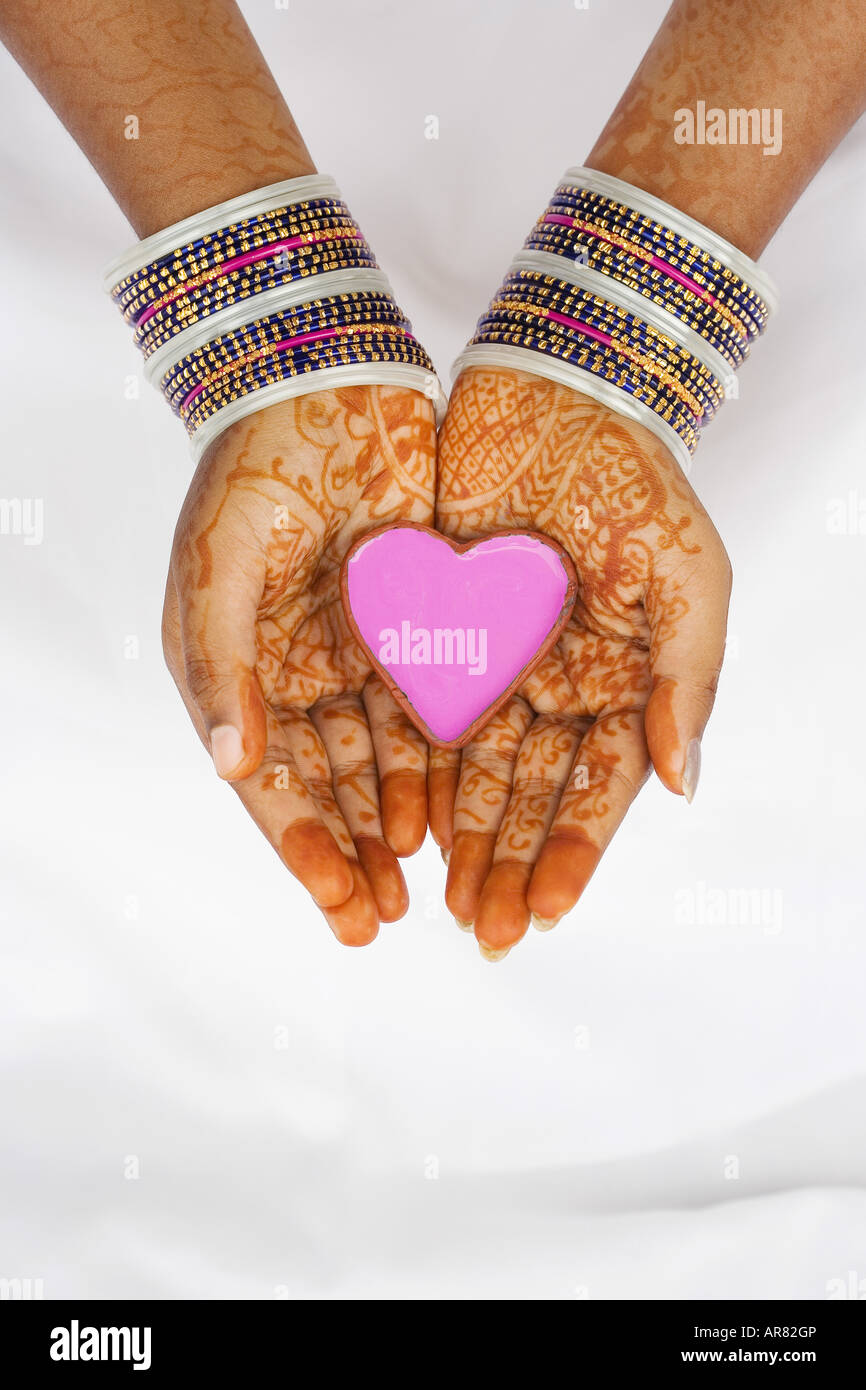 indian girl with henna hands holding pink heart shaped