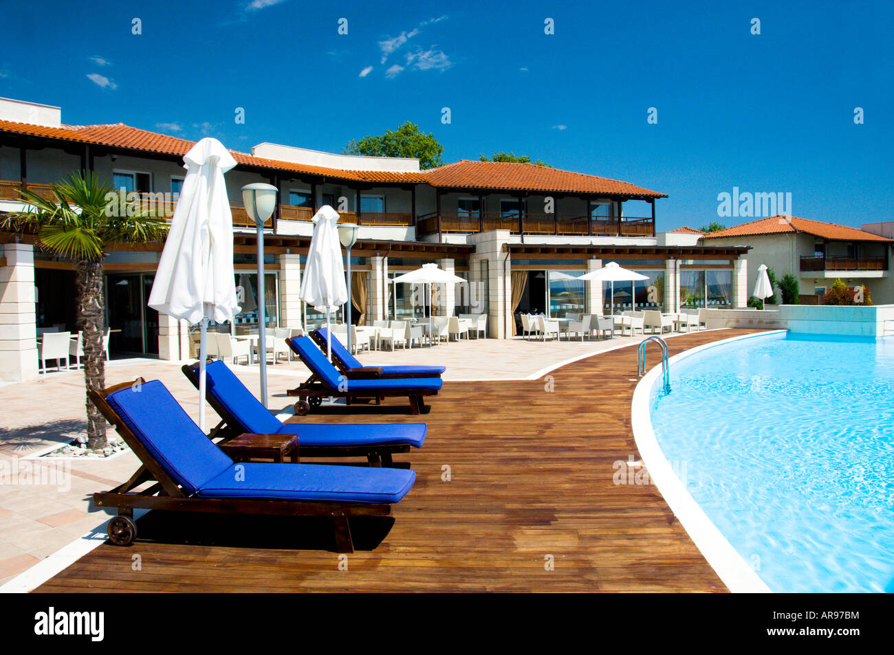 Pool Area With Blue Lounge Chairs At The Dion Palace Resort In Litohoro  Greece