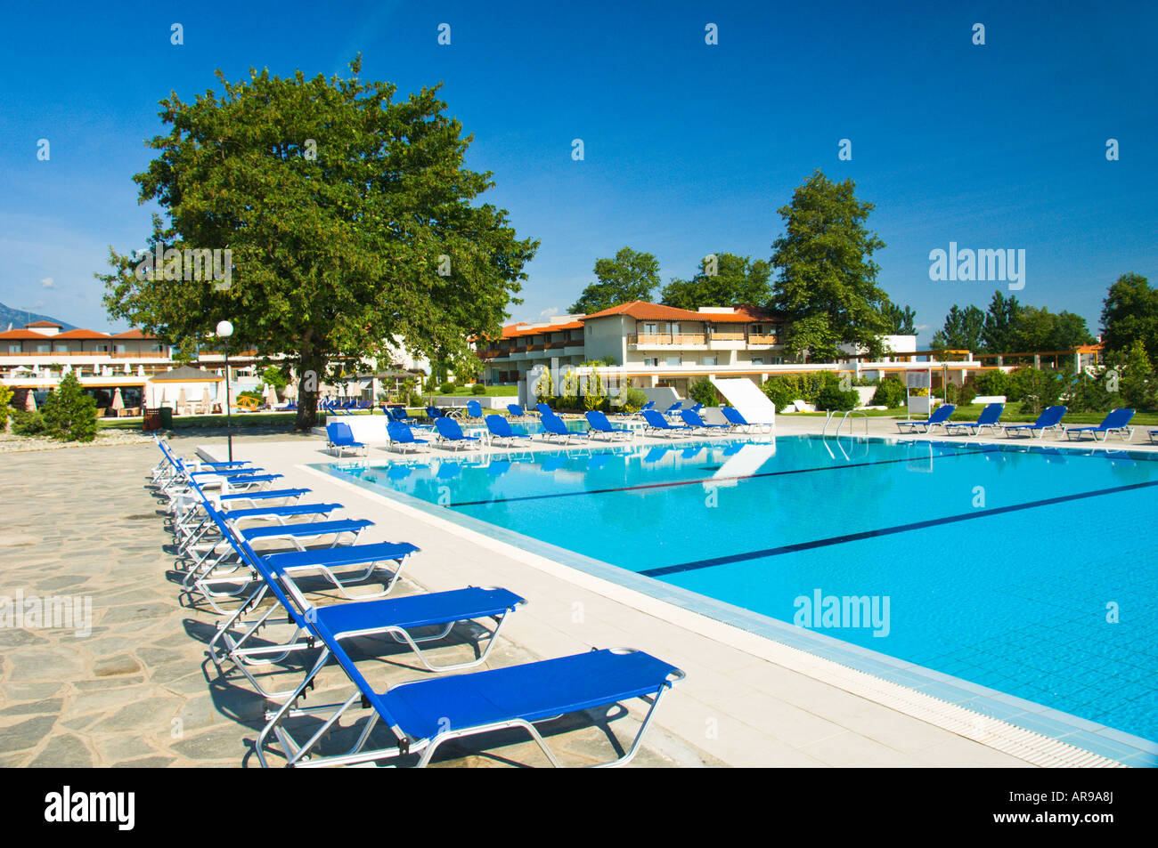 Pool Area With Blue Lounge Chairs At The Dion Palace Resort In Litohor  Greece