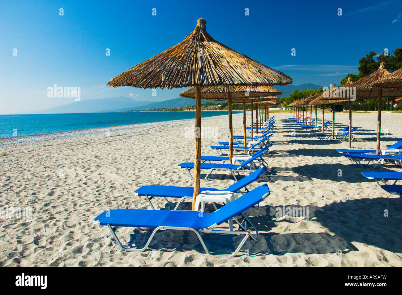 Stock Photo   Thatched Roof Umbrellas And Blue Lounge Chairs On The Beach  At The Dion Palace Resort In Litohor Greece