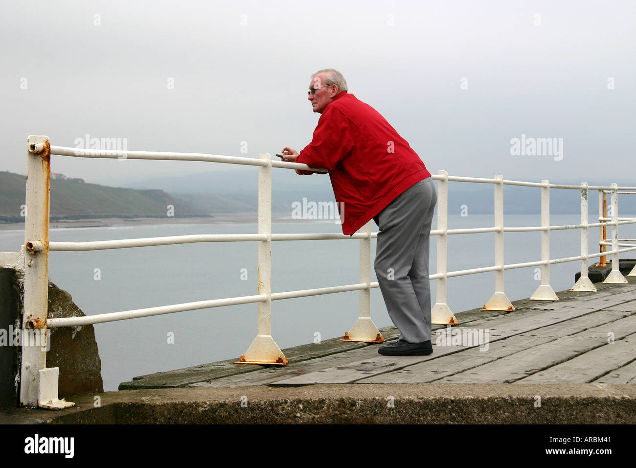 Man leaning on a pier safety handrail at Whitby, north Yorkshire ...
