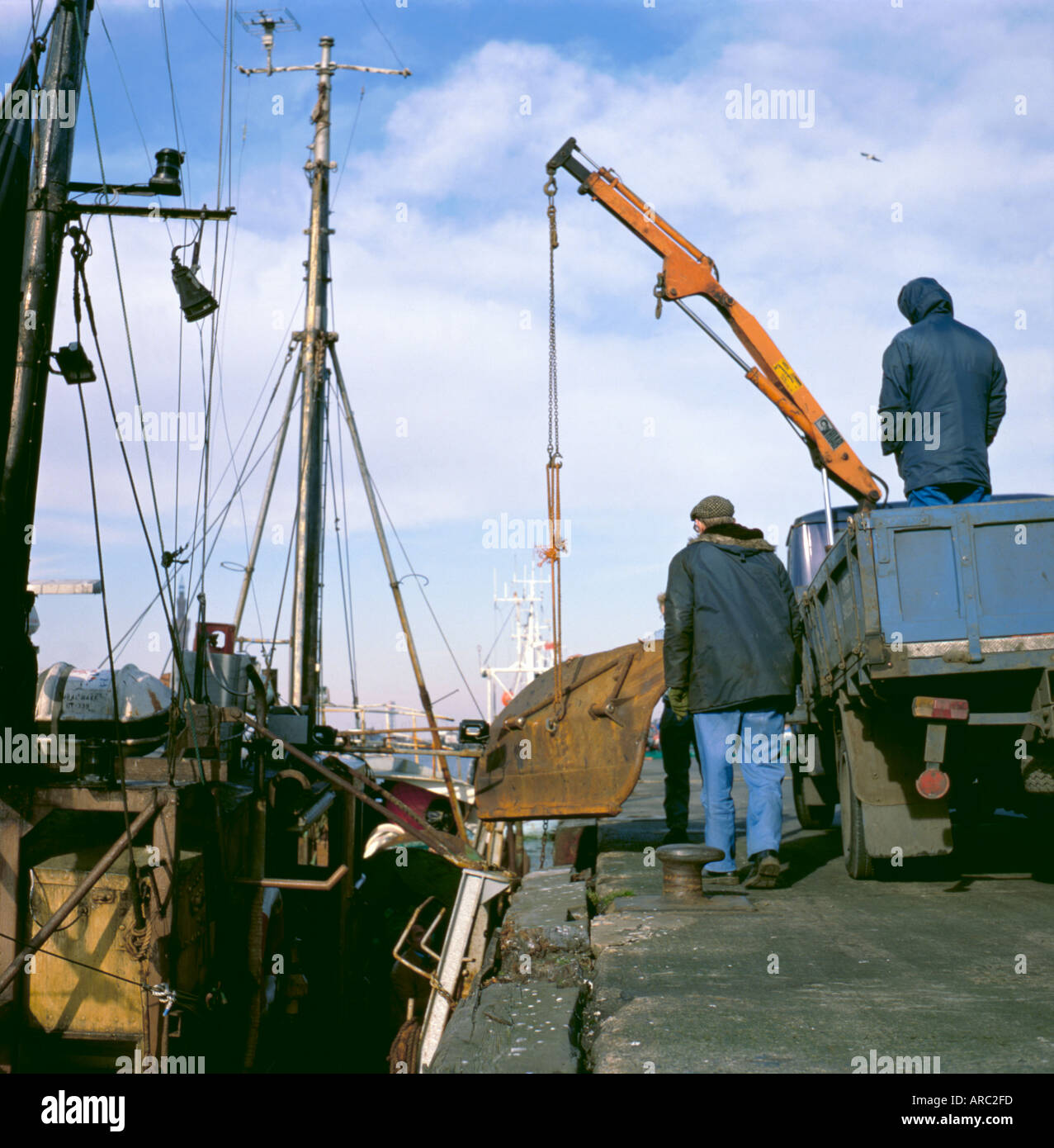 Small lorry mounted hydraulic crane being used to lift a trawl door ship repair yard Grimsby North Lincolnshire England UK & Small lorry mounted hydraulic crane being used to lift a trawl ...