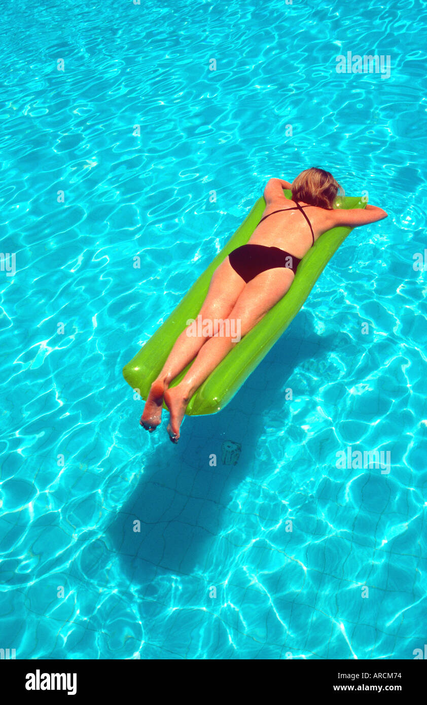 Inflatable bed clear - Stock Photo Woman 40 Floating On Inflatable Airbed Li Lo On Clear Blue Water Swimming Pool