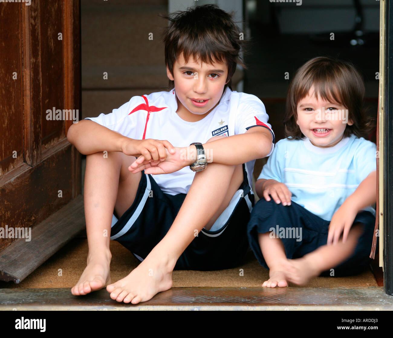 portrait  happy barefoot brunette boys sitting
