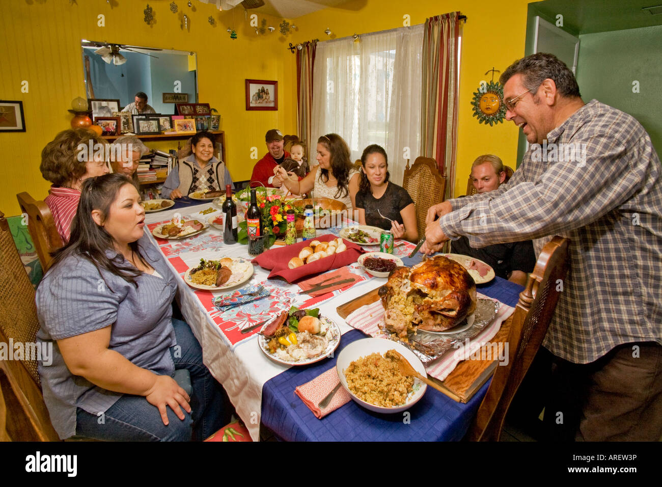 A Hispanic Father Carves The Turkey At Thanksgiving Dinner