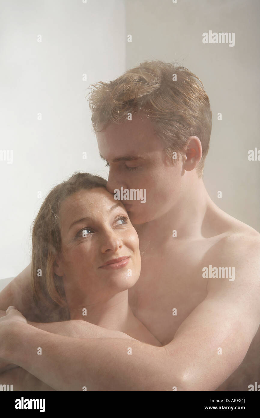 couple kissing in bathroom man kissing a woman in the bath stock photo