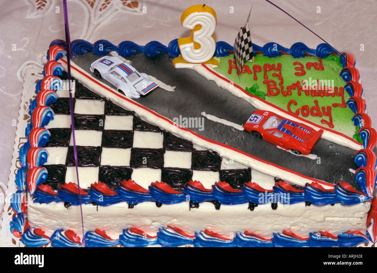 Race car cake waiting to be lit at 3 year old boys birthday party