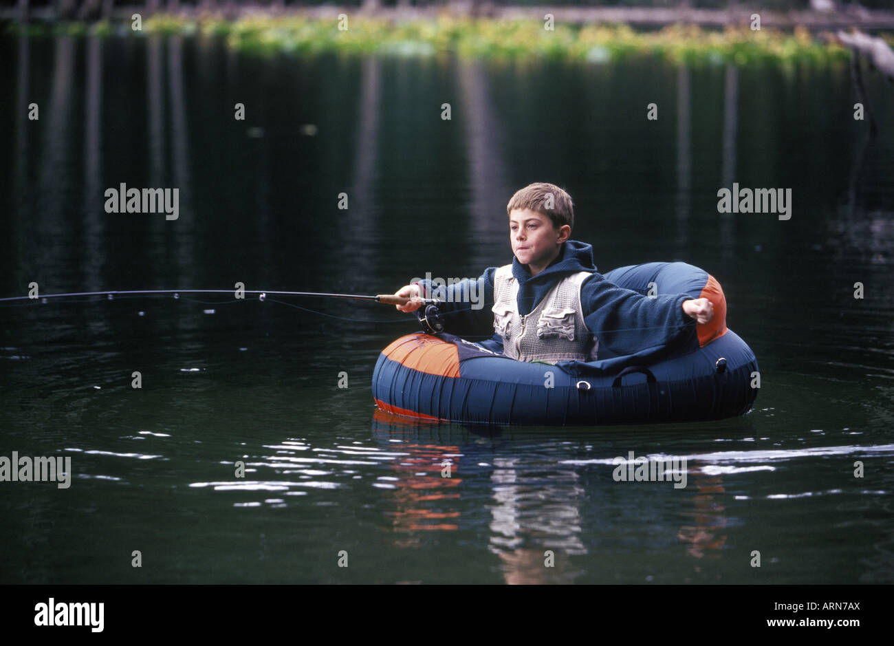 Boy fly fishing from float tube in small lake british for Fly fishing float tube