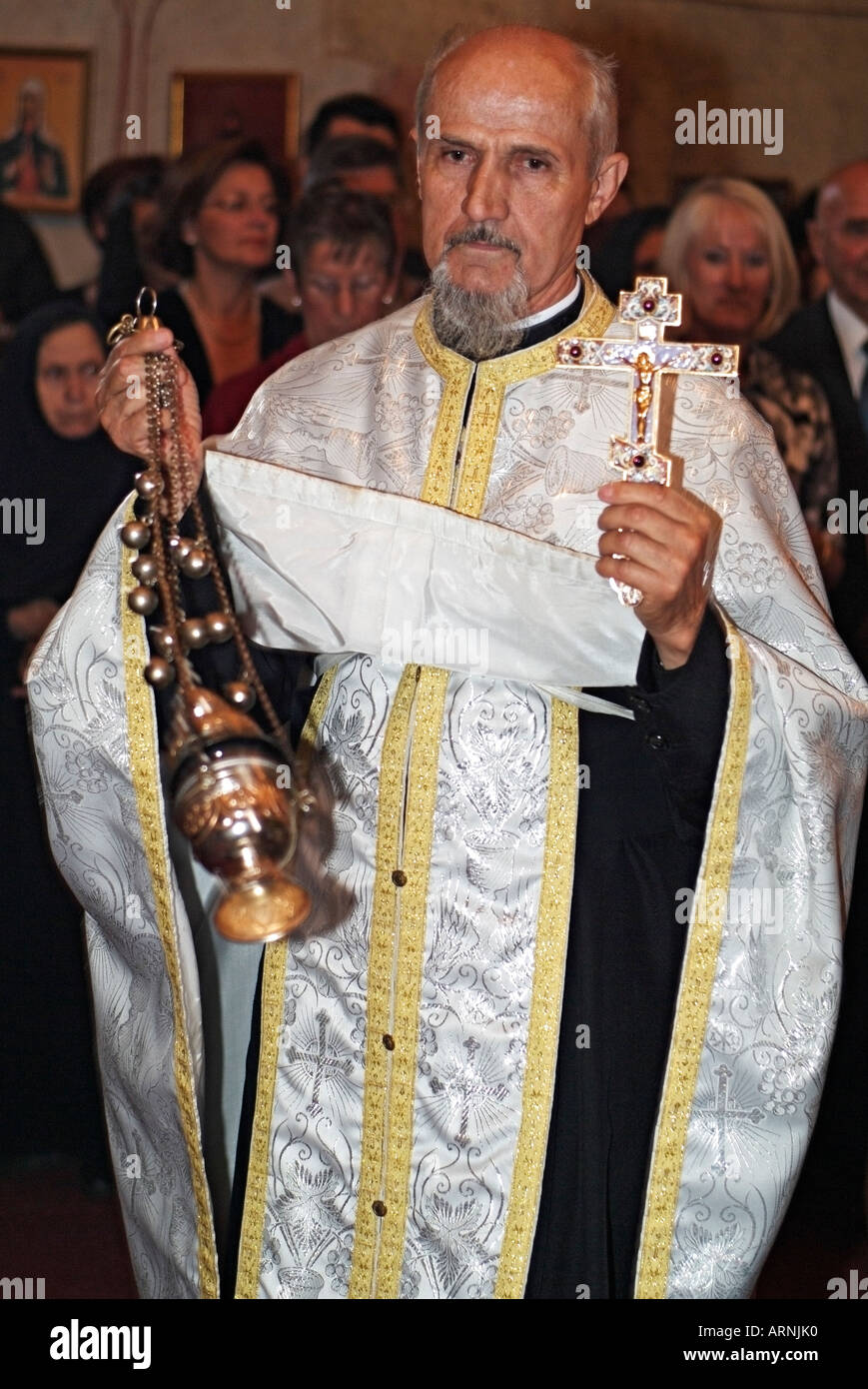 Eastern Orthodox Priest Swinging A Thurible With Burning Incense Inside To Cense The Congregation During Wedding Ceremony