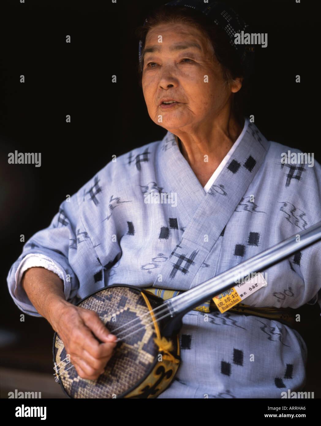 wearing a traditional yukata kimono plays shamisen an Okinawan sanshinTraditional Yukata