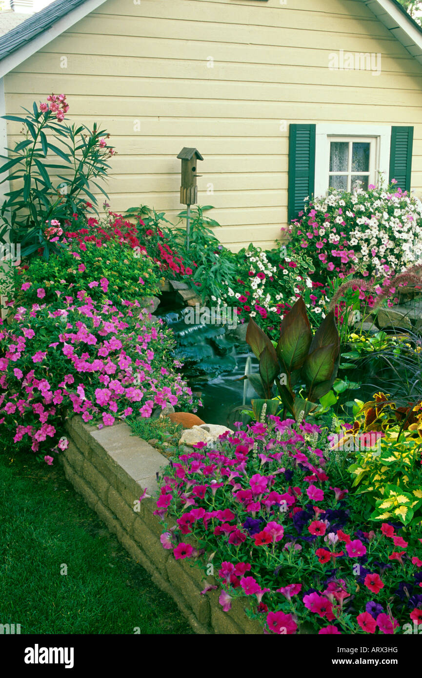 containers of annuals surround small pond and waterfall in