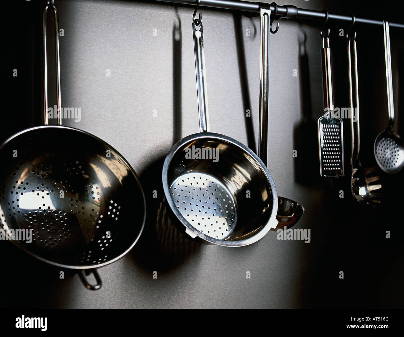 Pots Pans And Collinders Hanging Up In A Kitchen Stock
