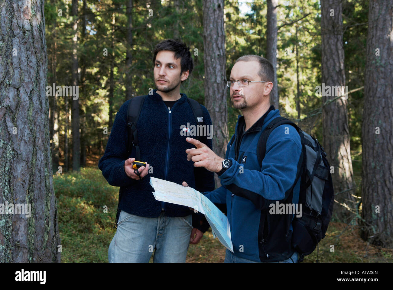 Male Hikers Verifying The Course With A Map And A GPS Receiver - Sweden map gps
