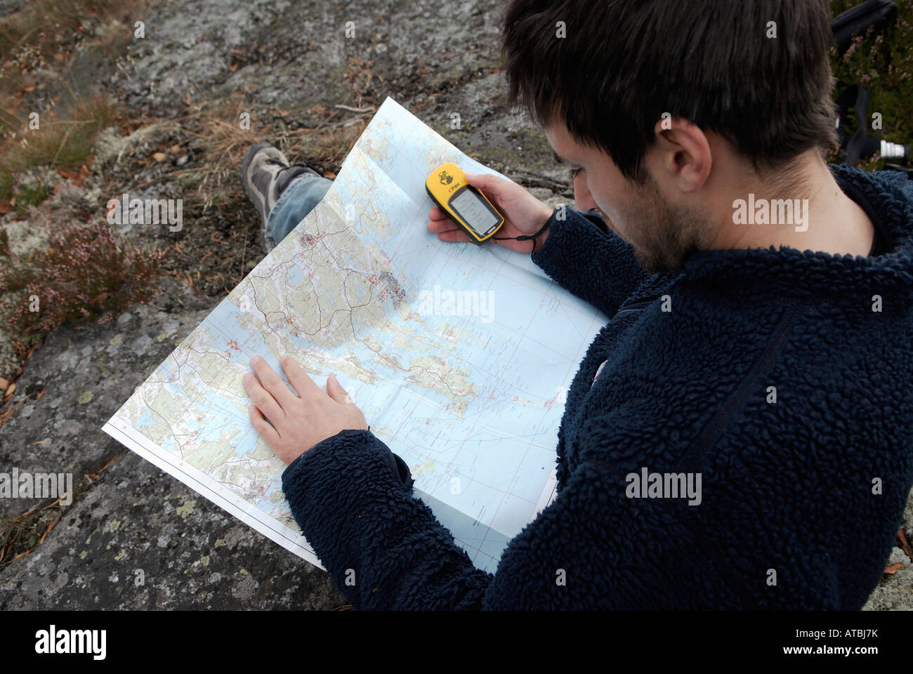 Young Hiker Verifying The Course With A Map And A GPS Receiver - Sweden map gps