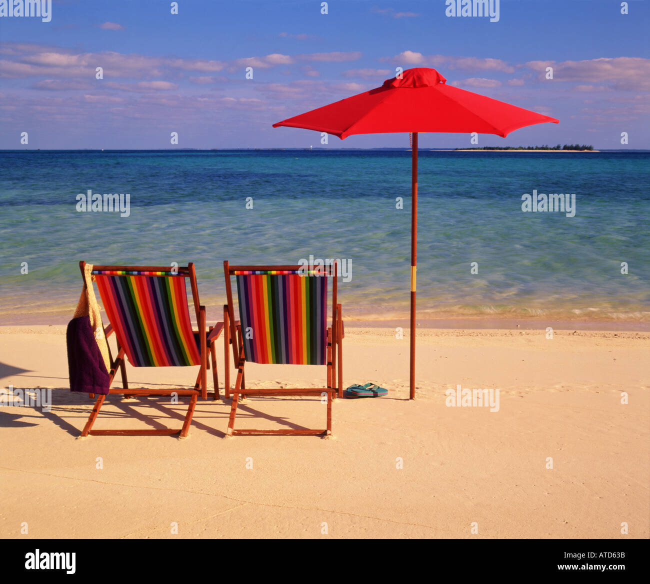 Tropical scene of two colorful beach chairs and an umbrella sitting Stock Royalty Free