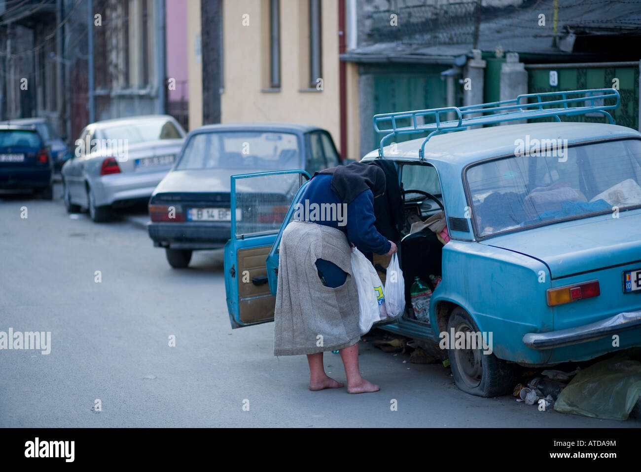 old poor woman without footwear near a cheap car with the front door ...