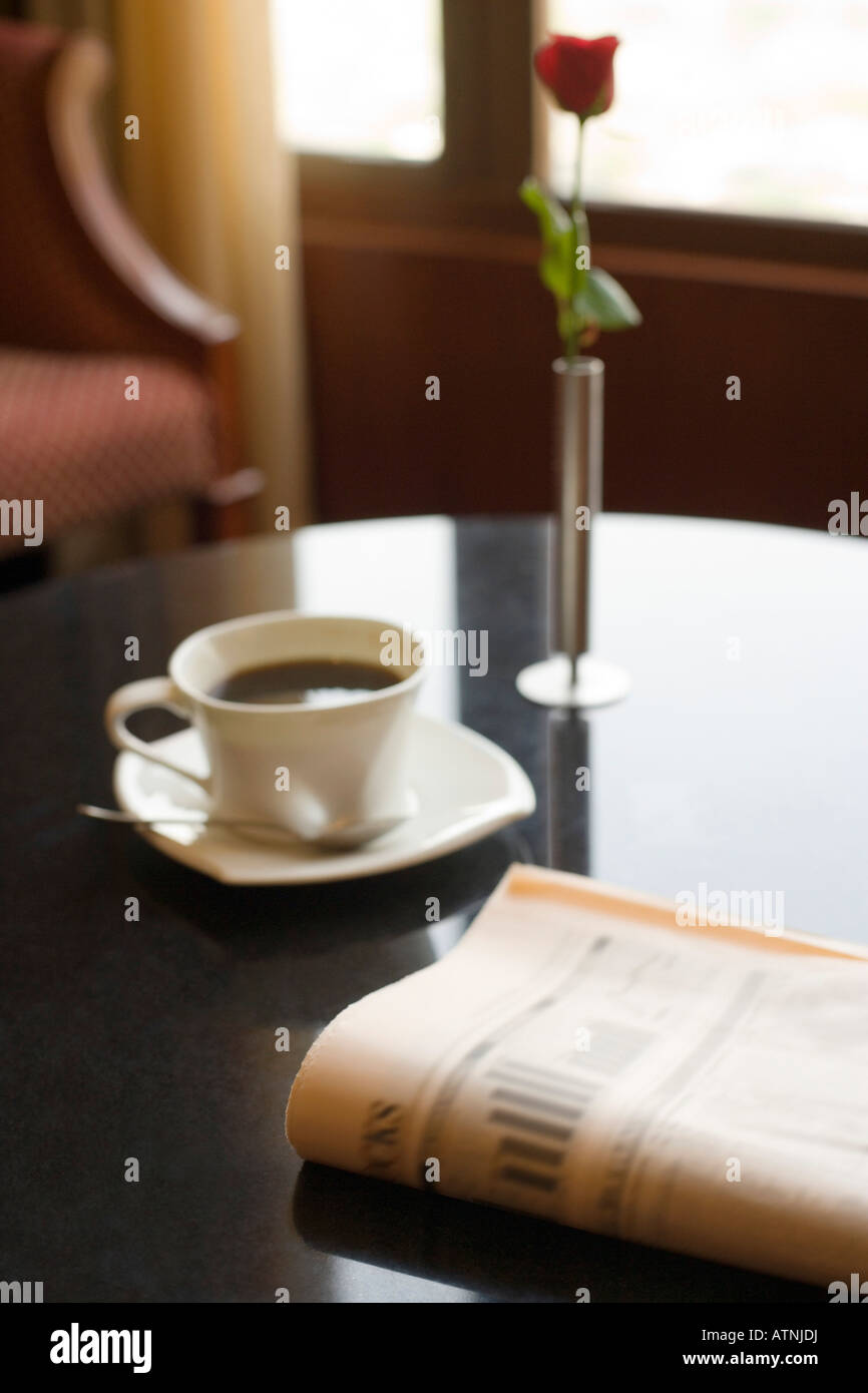 Coffee cup with a newspaper and a flower vase on a table stock coffee cup with a newspaper and a flower vase on a table geotapseo Gallery