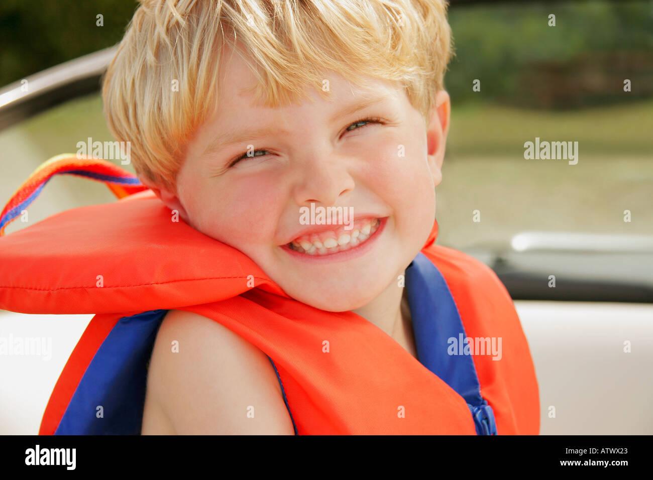A Happy Little Boy Wearing A Life Jacket Stock Photo
