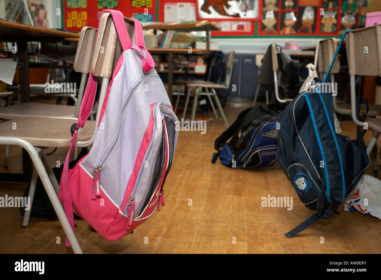 Girls And Boys Schoolbag Rucksacks Hanging Off The Back Of Empty Classroom Chairs In Primary School Belfast Northern Ireland