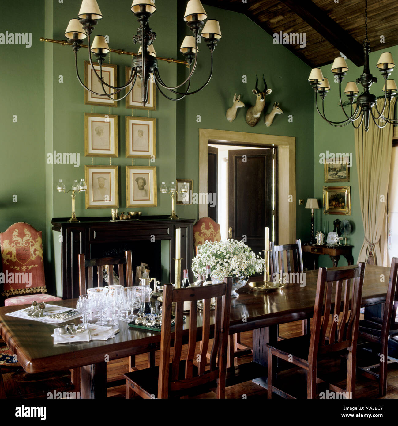 Dining Room With Green Walls And Wooden Furniture