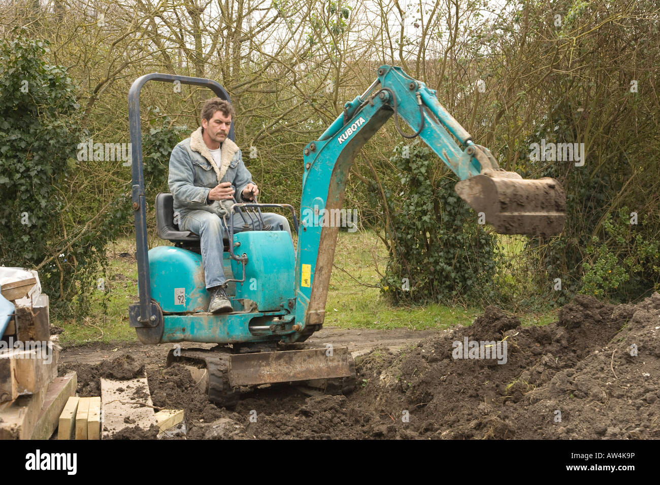Man On Bulldozer : A man driving mini digger excavator stock photo