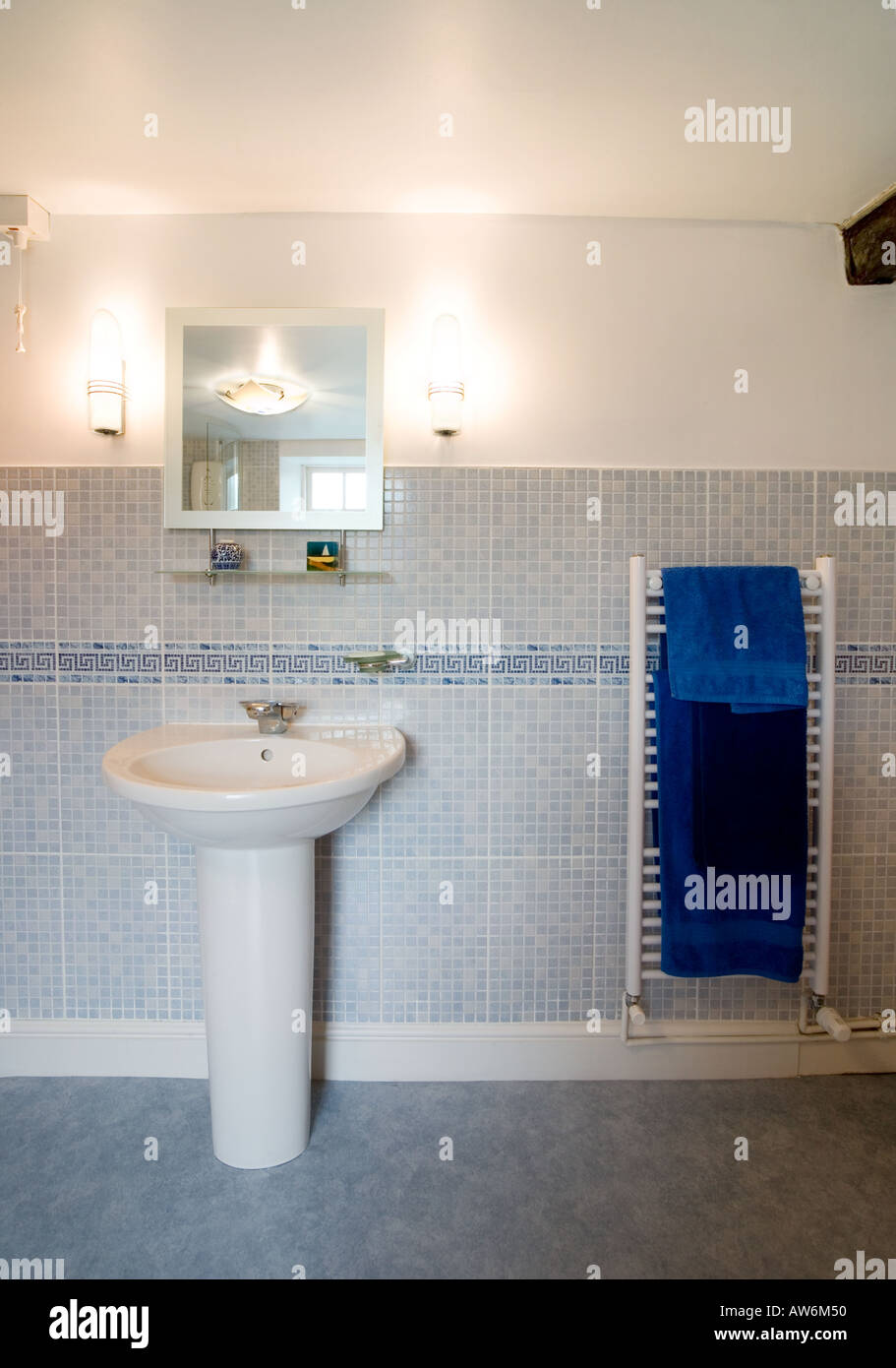 MODERN BATHROOM HAND BASIN WITH MIRROR AND WALL LIGHTS AND TOWEL RAIL WITH  BLUE TOWELS